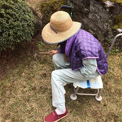 自宅にある農機具に座り、草取り